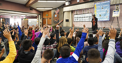 Students interact with The Sonnet Man at Gracey Elementary School in Merced.
